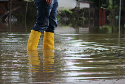 Person standing in flooded area with yellow rain boots on